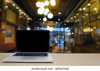 blank screen display laptop on wooden table with blurred background of coffee shop with empty people for co work space; out side office conceptual
