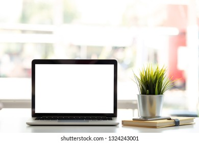 Blank screen Laptop computer and poster workspace background in modern office