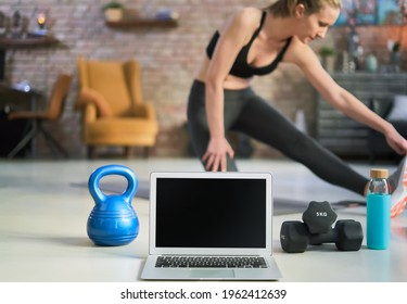 Blank screen laptop and fitness equipments at home. Concepts about online workout program, fitness video program, home workout.