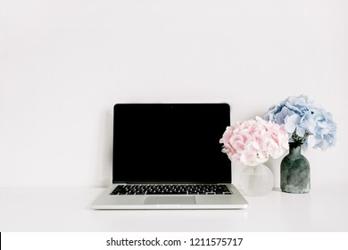 Blank screen laptop and pink and blue hydrangea flower bouquets on white background. Minimal home office desk workspace.