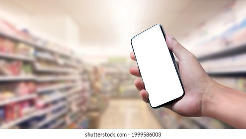 Blank screen of Mobile phone with hand holding phone on Soft blurry Supermarket store background. of free space for copy and Branding.