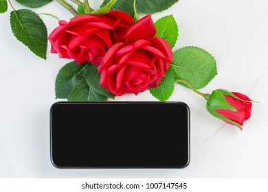 Blank screen of new Smartphone iPhone next to red roses on marble background, conceptual for giving gift to lover on Valentine's day