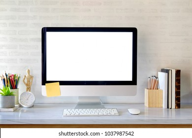 Blank screen on the desktop computer with house plant and office supplies, mock up