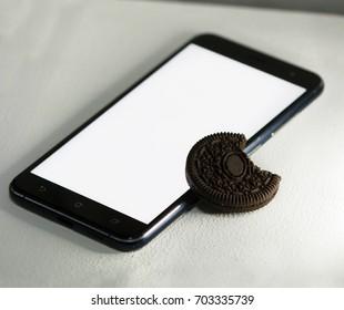 blank screen smart phone with black sweet cookie