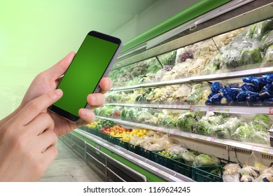 blank screen smart phone on blurred vegetables shelf.