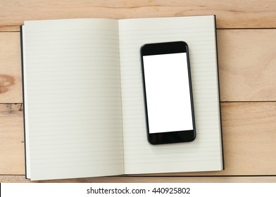 Blank screen smartphone with notebook on wooden background