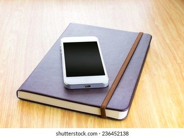 Blank screen Smartphone on Brown Hard cover notebook with elastic strap on wooden table in perspective view,Template for adding your content