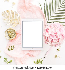 Blank screen tablet, pink hydrangea flowers bouquet, tropical palm leaf, pastel blanket, monstera leaf plate and accessories on white background. Flat lay, top view rose gold home office desk