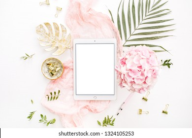 Blank screen tablet, pink hydrangea flowers bouquet, tropical palm leaf, pastel blanket, monstera leaf plate and accessories on white background. Flat lay, top view