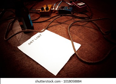 Blank set list on a stage for live performance with guitar instrument cable, guitar effects pedals and beer bottle