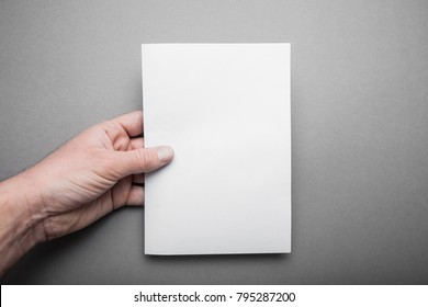 Blank sheet A5 for design, a mock-up in the hand of a European man.