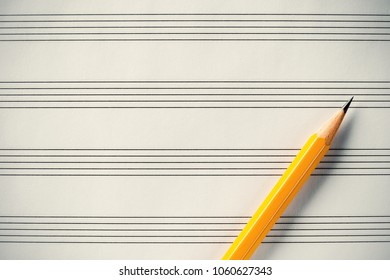 Blank sheet music and pencil