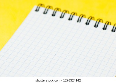 Blank sheet of a notebook (squared), on yellow background
