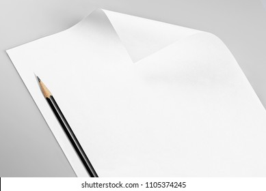 Blank sheet of paper with curled corner and pencil, over gray background