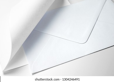 Blank sheet of paper with curled corner and envelope