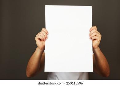 Blank sheet of paper in male hands on dark background