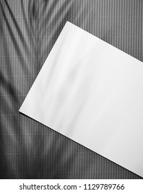 Blank sheet of paper on dark wooden table background with leaves shadows . White paper with plenty of copy space. Top view.