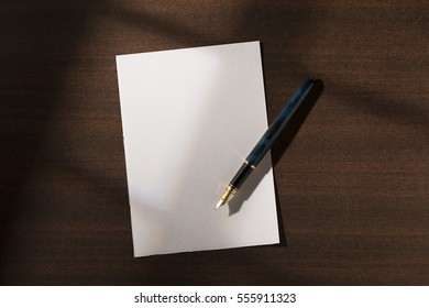 Blank sheet of paper on the table with pen