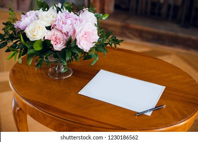 Blank sheet of paper, pan and beautiful flower bouquet on the vintage wooden table. Wedding concept. Vow