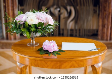Blank sheet of paper, pan and beautiful flower bouquet on the vintage wooden table. Wedding concept. Writing vow