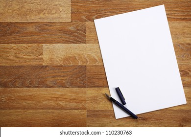 Blank sheet of paper and pen on bright wooden office desk.