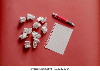 Blank sheet of paper, pen and scraps of crumpled paper balls on a coral background with shadows. A page torn from a spring-loaded notebook and scraps of white paper. Top view at an angle.