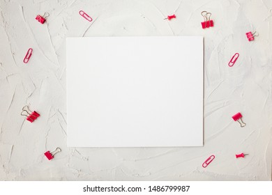 Blank sheet for to-do list or plans, stationery around. Copy space ,white background in the center, gray cement background, pink paper clips around