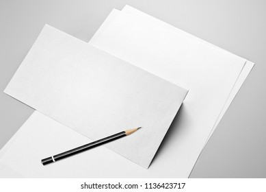 Blank sheets of paper, envelope, and pencil