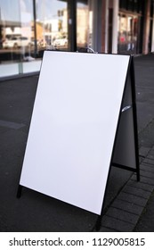 A blank shop sign board in rectangle shape on a street pavement ready for copy text.