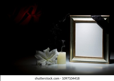 Blank shyning mourning frame, with smoky candle and white lily flower on dark background with red decoration