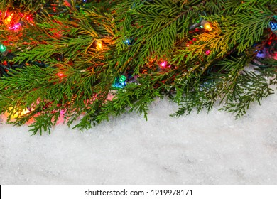 Blank sign with Christmas tree garland and colorful string of lights border; holiday background with white copy space