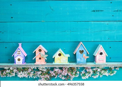 Blank sign with colorful birdhouses with butterfly on shelf by spring tree flowers on antique rustic wood background; pink, yellow, purple, orange birdhouses with teal blue copy space