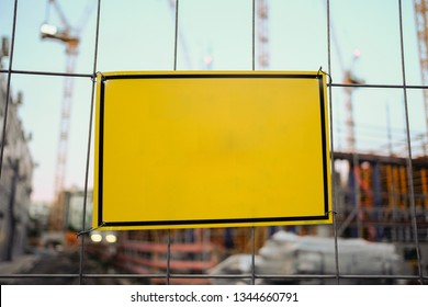 Blank sign hanging on fence at construction site - empty sign mockup