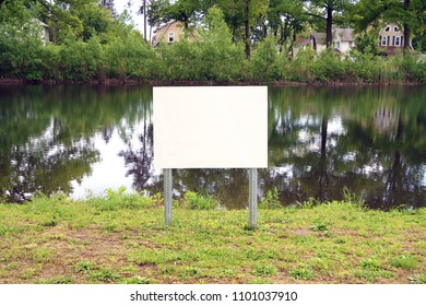 Blank sign next to a lake in a park. Template.