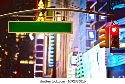 Blank sign and red stop light on Broadway in New York City at night