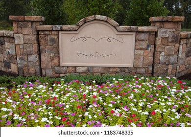Blank Sign In a Rock Wall Surrounded by Flowers and Trees