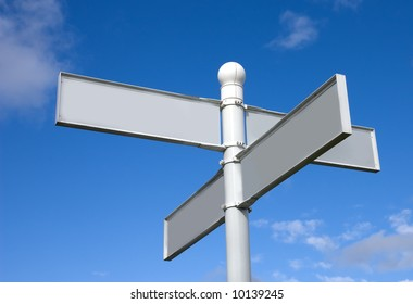 Blank signpost with four direction pointers against a blue sky