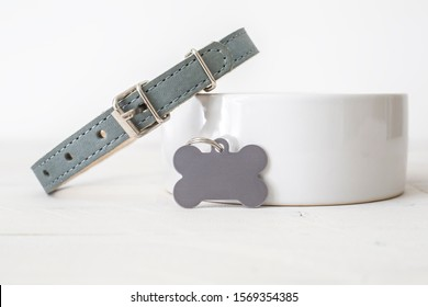 Blank silver bone dog tag on white background leaning on dog bowl with dog collar, dog tag mockup