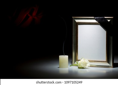 Blank silver mourning frame, with smoky candle and white rose, on dark background with red decoration