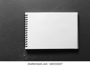 Blank sketchbook with white pages isolated on black background