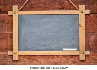blank slate blackboard hanging on a rustic barn wood wall painted red
