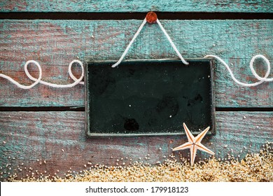 Blank slate for your seafood menu or advertisement hanging on grungy weathered blue wooden boards with sea sand and a starfish in a pretty marine background