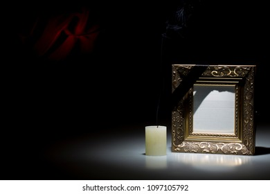 Blank small golden mourning frame with smoky candle on dark background with red decoration