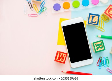 blank smart phone with pencils,wooden alphabet block,clipper,water color palete,pin,smart phone,water color palete on pink pastel background.flat lay, top view. Back to school concept