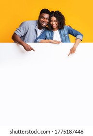 Blank Smiling Couple Pointing At Blank Advertisement Board, Recommending Something, Free Space For Text
