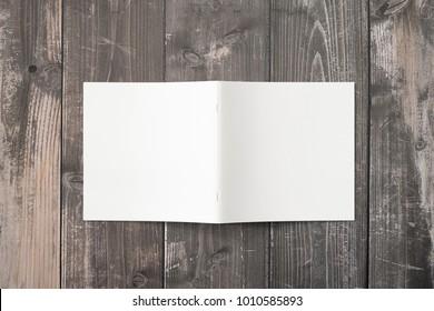 Blank soft cover of square magazine or brochure on wooden desk. 3d Illustration for your presentation.