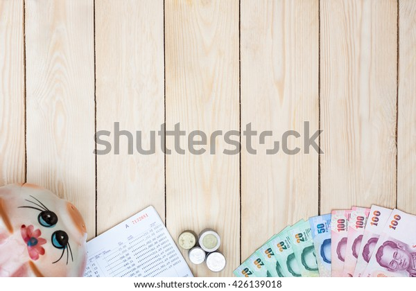 Blank space with money and saving account passbook, Book bank statement in the middle of office equipment on office desk. Finance wooden background. Top view.