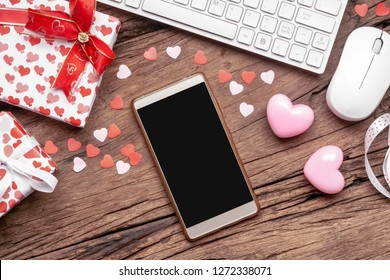 Blank space smartphone mock up template for Valentine's day internet online shopping concept. Flat lay top view with heart shapes, gift boxes, keyboard, mouse and blank space smartphone.