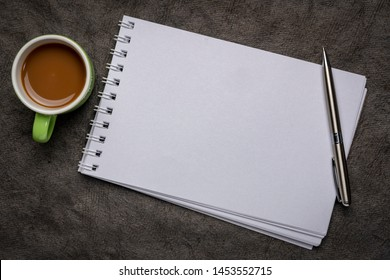 blank spiral art sketchbook against against textured bark paper with a cup of coffee