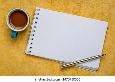 blank spiral art sketchbook against yellow textured bark paper with a cup of coffee